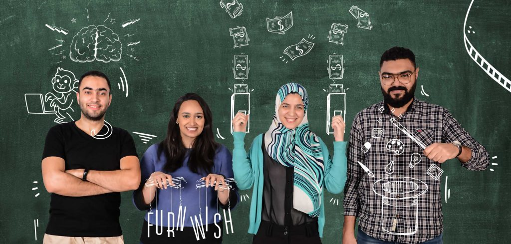 Image description: The founders of Furnwish, two men and two women stand in front of a blackboard.