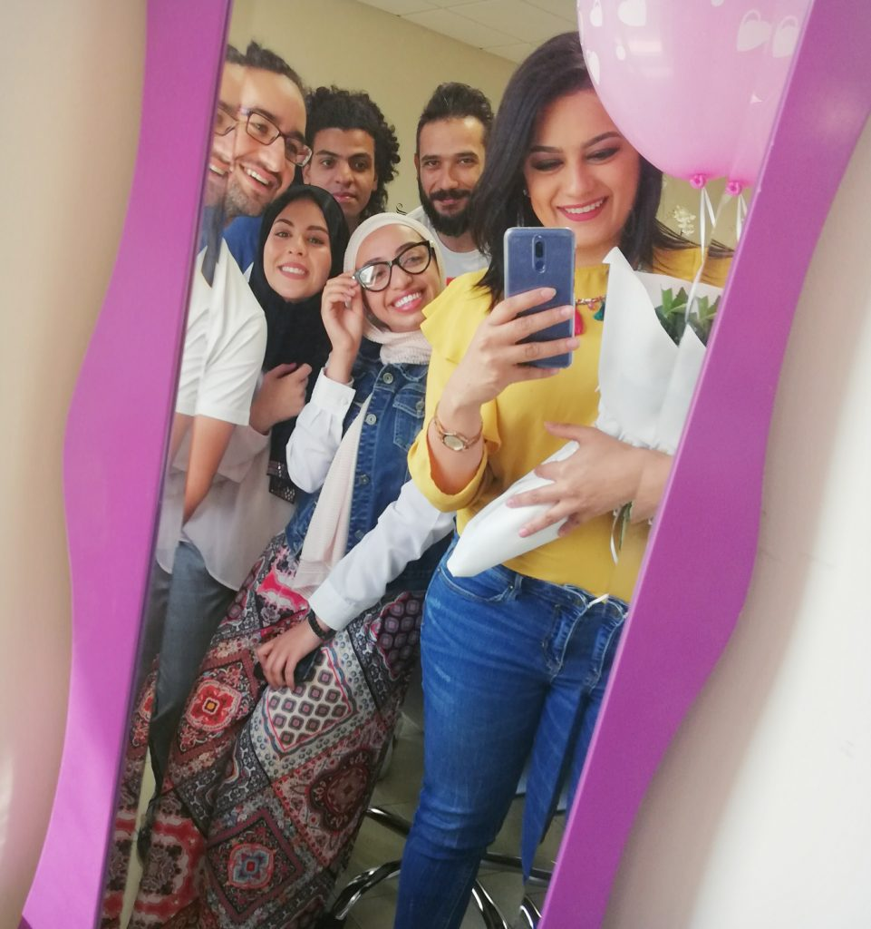 Image description: The founders of Myrati, three men and three women crowd in to take a selfie together in a mirror.