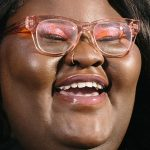 [Image Description: Rochelle Brock is smiling and laughing, she is wearing pink glasses.]