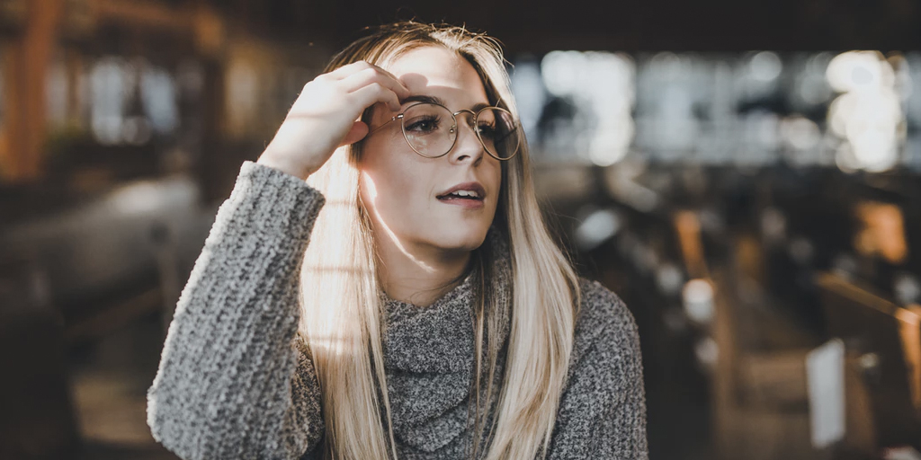 A woman in glasses looking to the side.