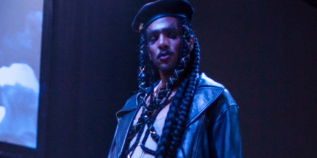 A person with long braided hair and a mustache dressed in a black leather jacket and black beret stands against a dark backdrop.