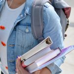 Image description: A person wearing a denim jacket and backpack holds a few textbooks in their hands.