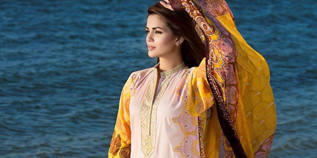 A woman wearing a yellow Salwar Kameez looking past the camera and towards the ocean.