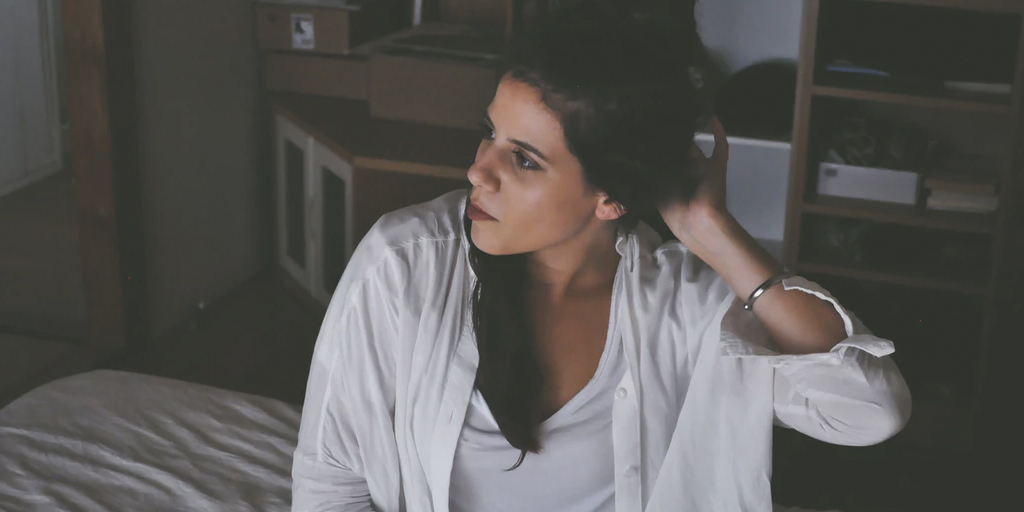 A girl is sitting on a bed, looking pensive.