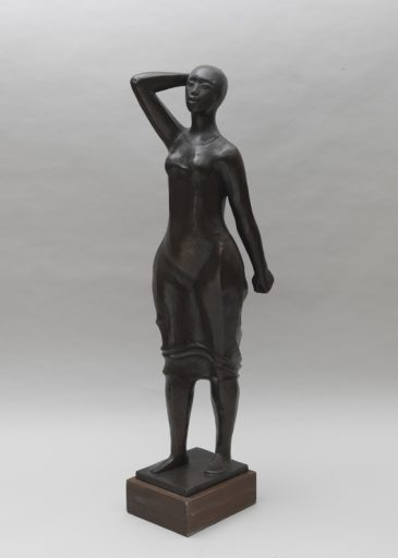 Bronze statue of smiling full-bodied woman standing with one arm behind her head and one arm at her side.