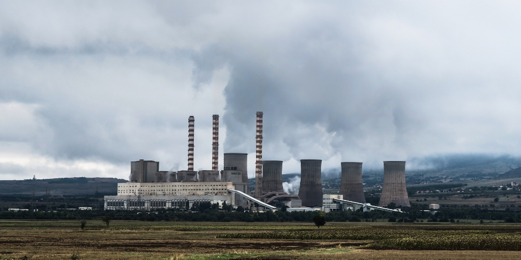 A power plant facility that has smoke coming out of it. Behind it are overcast grey clouds and grassy hills. In front of the facility are fields
