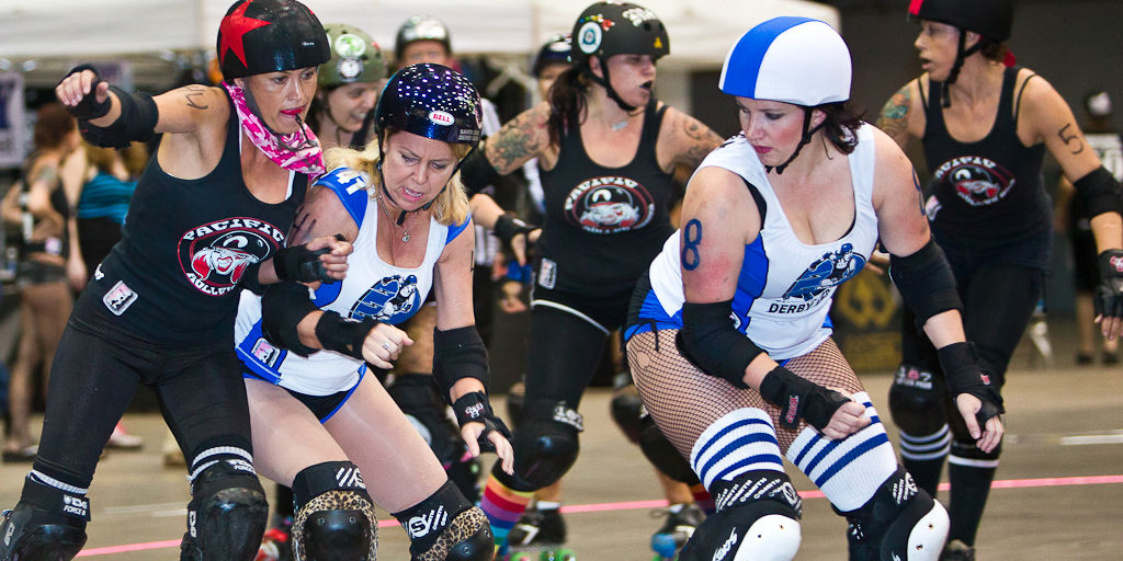 Women with protective equipment play roller derby.