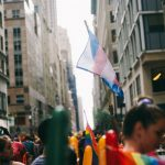 A parade of people with someone waving the Transgender flag, a flag with blue, pink and white stripes.