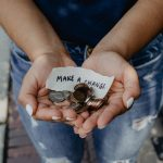 """Hands holding coins and a piece of paper with """"make a change"""" written on it. Legs in jeans below the hands."""