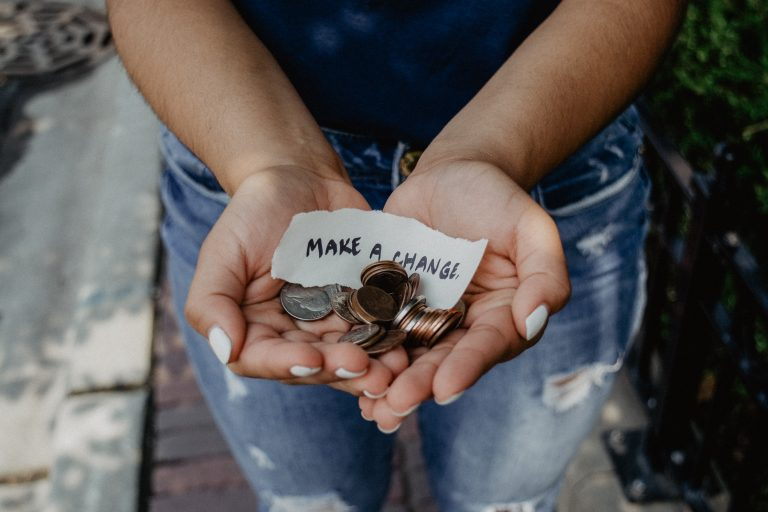 "Hands holding coins and a piece of paper with ""make a change"" written on it. Legs in jeans below the hands."