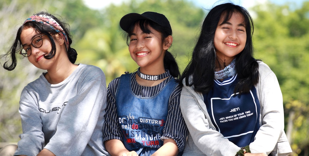 Three teen girls smile at the camera. they're so cute.