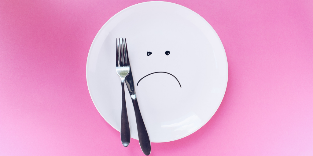 [Image description: A white plate on a pink background. A sad face is drawn on the plate, and a knife and fork rests on the plate.] via Unsplash
