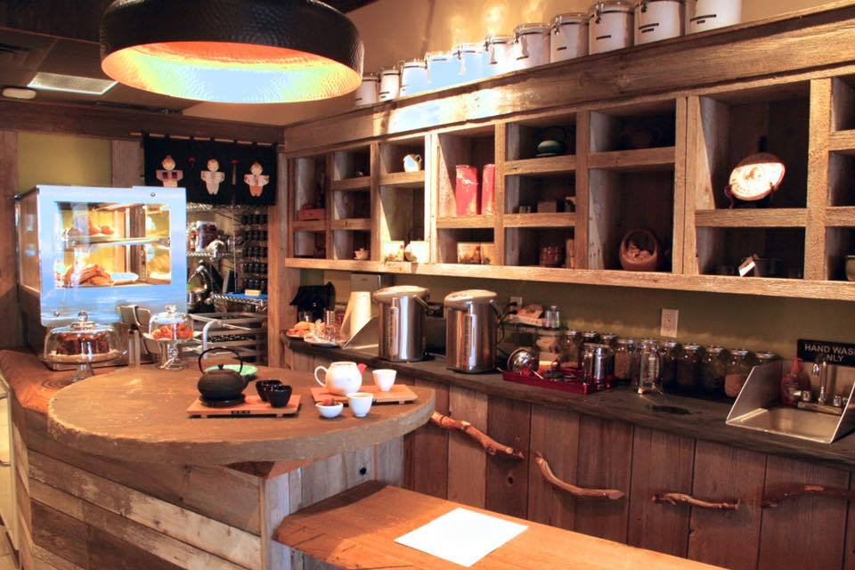 A tea shop with wooden cabinets, bookshelves and bar. Metal tea canisters, jars, and hot water heaters sit on the shelves. On the left is a round stone countertop.
