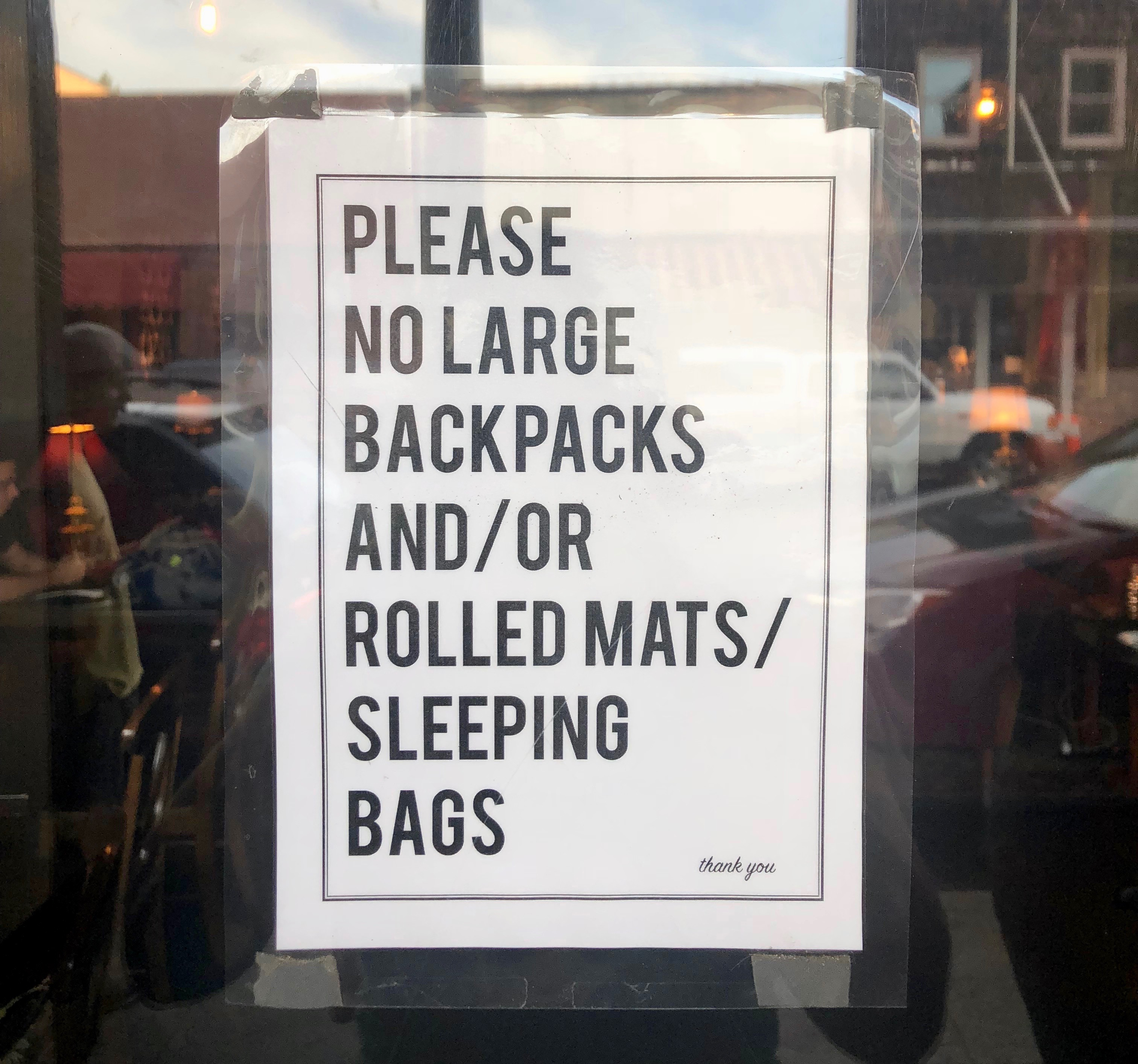 "White sign with black letters posted on glass saying ""Please no large backpacks and/or rolled mats/sleeping bags. thank you."""