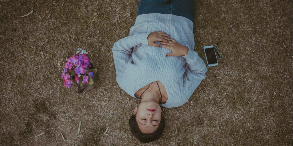 A woman lies on the ground outside with her eyes closed and her hands resting on her belly. She wears a light blue sweater, jeans, and has dark brown hair and black painted nails. On her right is a cell phone and on her left is a bunch of white and pink flowers.