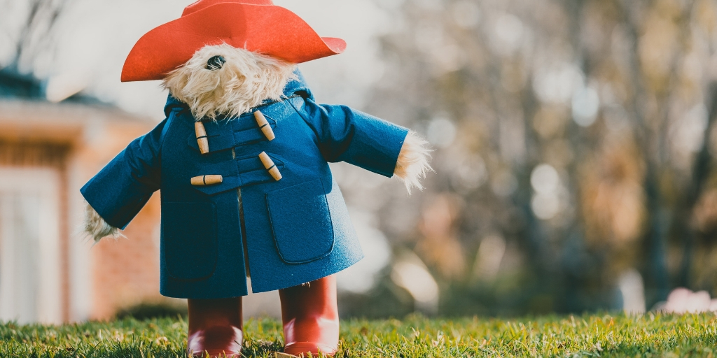 A stuffed Paddington Bear stands on a lawn. He wears a wide brimmed red hat, a long wool jacket, and red boots. He has light brown colored fur