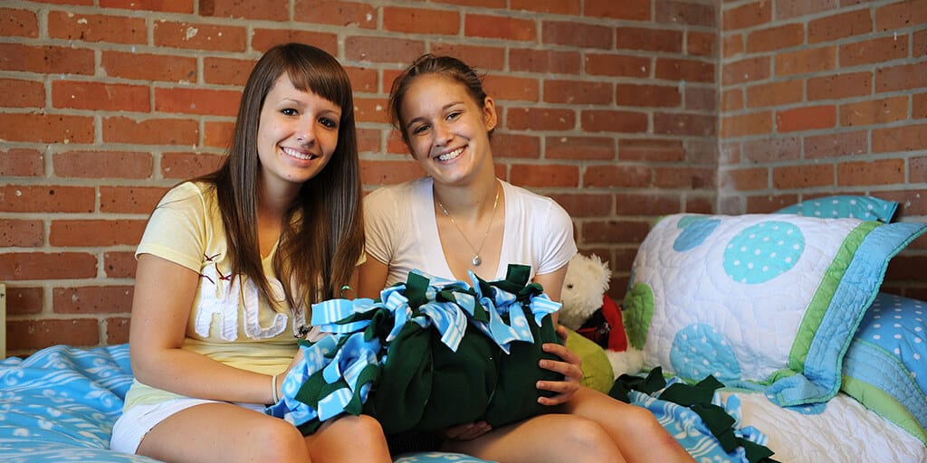 Two young women are sitting on dorm bed, holding a pillow and smiling.