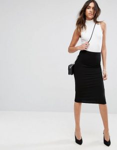 A woman wearing a black pencil skirt with a white top and a purse.