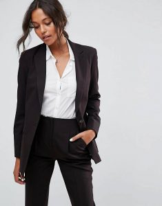 A woman wearing a black blazer, black slacks and a white shirt.