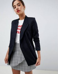 A woman wearing a black blazer, a graphic t-shirt and a grey plaid skirt.