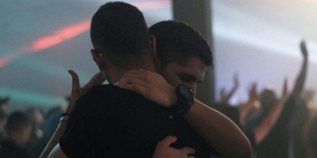 Two boys hugging in a bar.