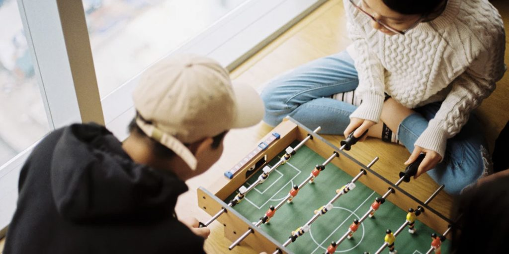 A man and woman playing at a foosball table.