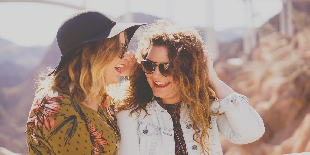 An image of two women wearing sunglasses and laughing.