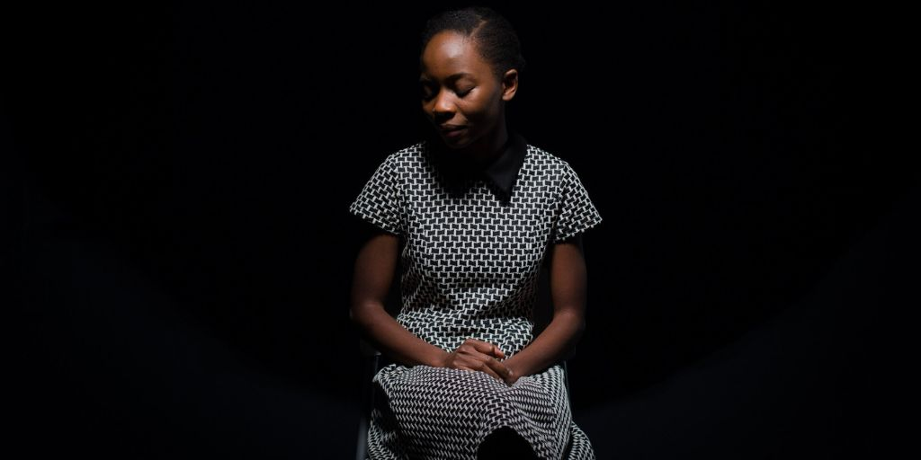 A young black woman, wearing a polka dot dress is sitting and looking to her right.