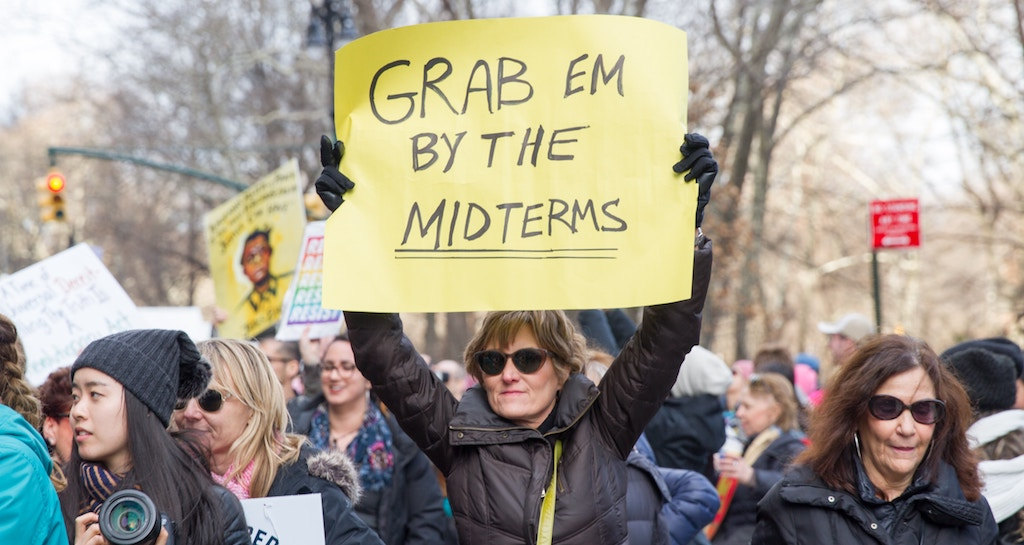 [Image description: women's march shot. Woman holding up a sign that reads 'GRAB EM BY THE MIDTERMS.'] original image via Unsplash