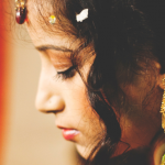 [Image description: A side view of a brown, dark haired woman wearing a gold jhumka] via Unsplash.