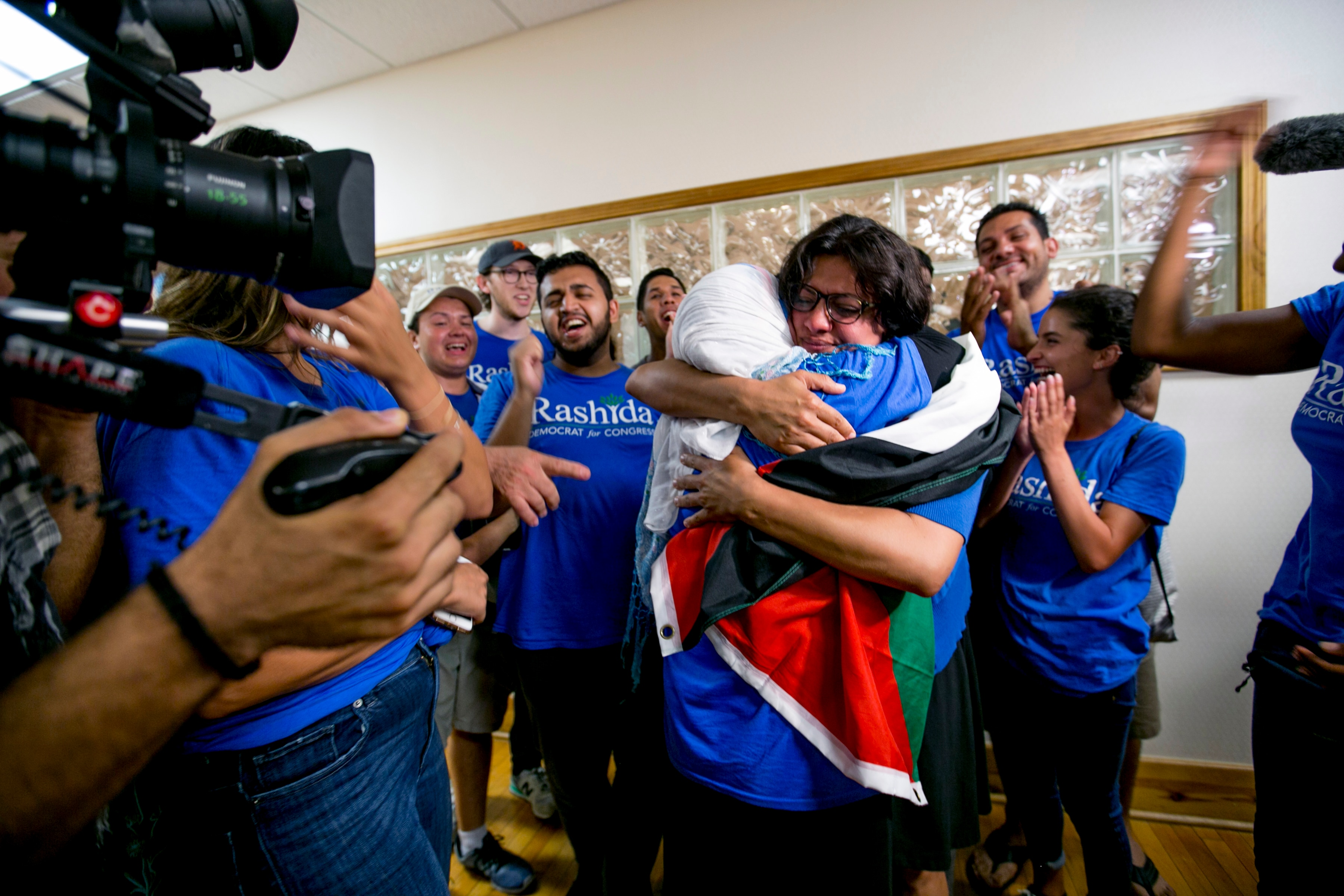 [Image Description: Rashida Tlaib draped in a Palestinian flag is embracing her mother on the night of her Primary Election win.]