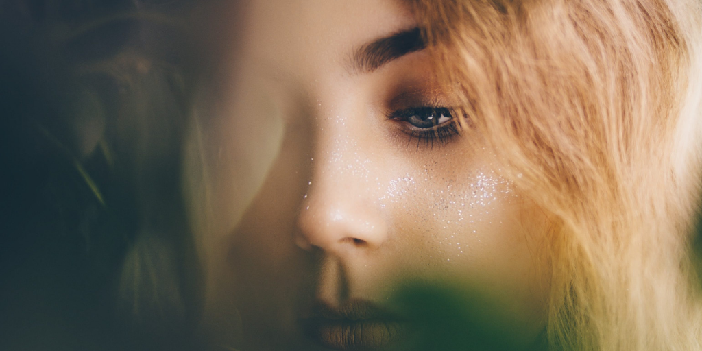 [Image description: A hazy close up of a woman's face with with her looking down.] Via Unsplash.