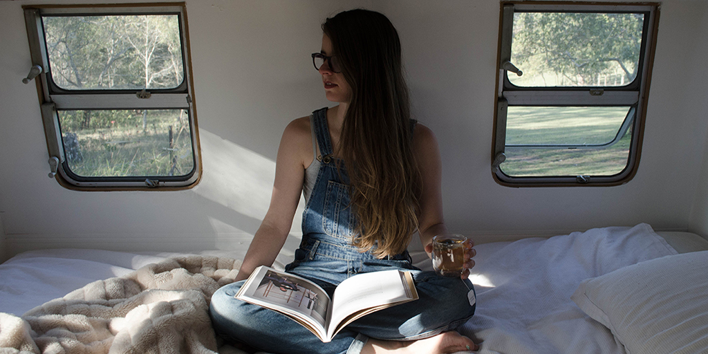 A girl with pale skin and long brown hair sitting in bed with a book in her lap.