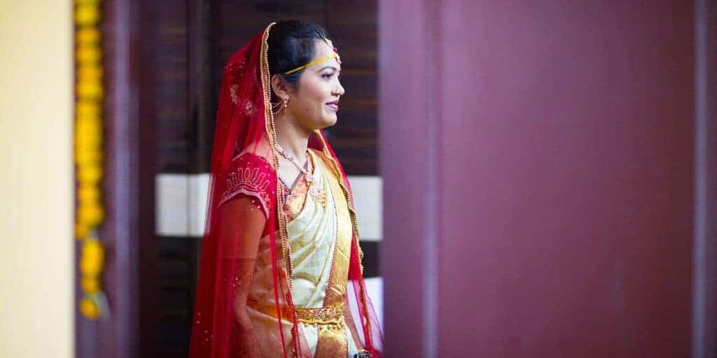 An Asian woman is facing to the right. She is smiling and dressed in a red-and-gold bridal dress.