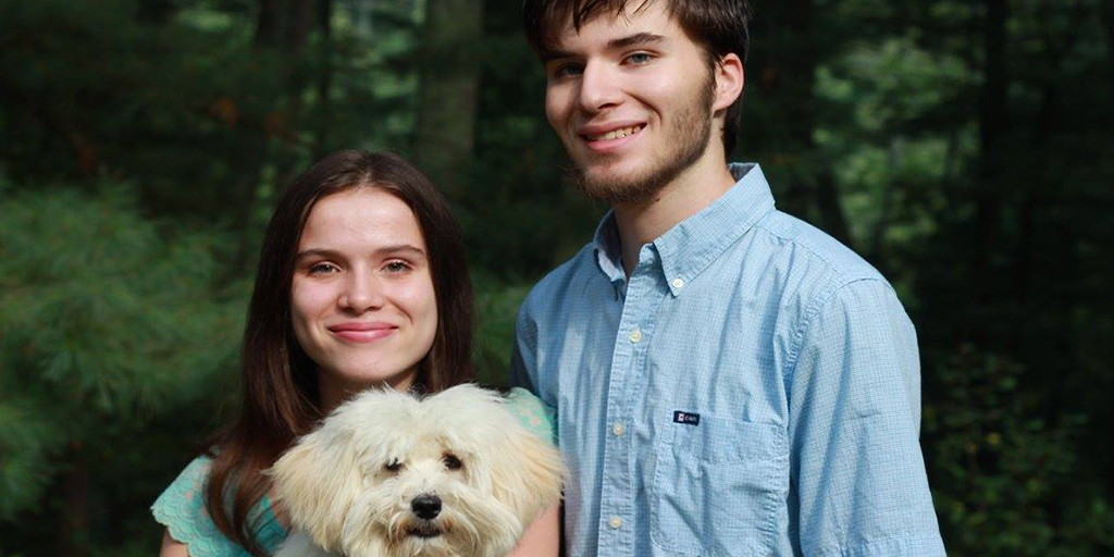 Julia and David Metraux stand in front of trees in their backyard with their dog Lucky.