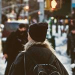 A girl in a hat walks down a busy city street in the winter.