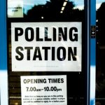 """A picture of a window with a sign reading """"POLLING STATION"""""""