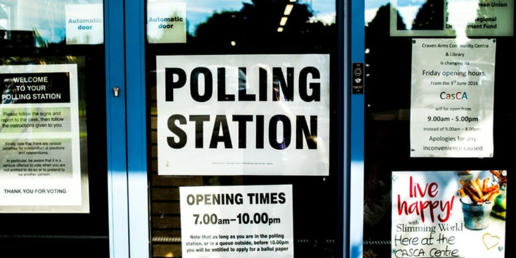 "A picture of a window with a sign reading ""POLLING STATION"""