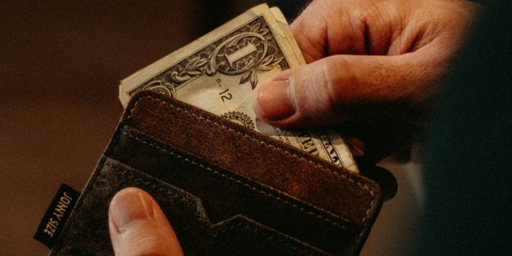 A person pulling a $1 bank note out of a wallet.