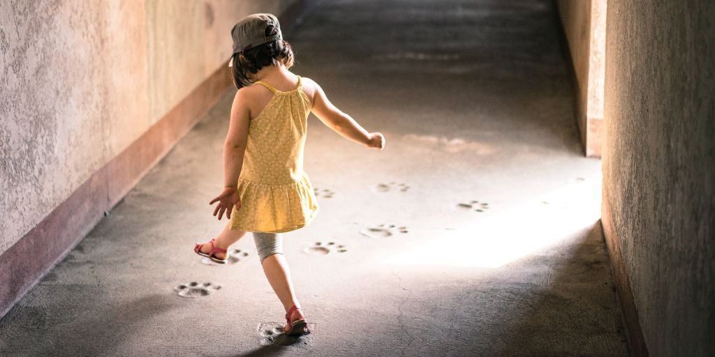 A little girl in a yellow dress, gray hat, light gray shorts, and red sandals is stepping on paw prints along a hallway.