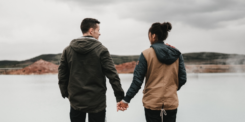 A man and a woman stand, holding hands on an overlook of water and rolling hills. The man standing on the left turns to the woman standing to his right and is smiling. He has dark, closely cropped hair and is wearing a green jacket. The woman looks out to the left but can't see her expression. She has black hair pulled into a bun and is wearing a brown jacket with green sleeves that has tie in back