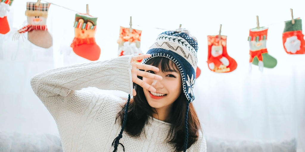 A woman with long brown hair, wearing a white sweater and wool hat with tassels on the ear flaps, smiles and holds her hand in front of her face with her fingers spread wide. Behind her red Christmas stockings hang on a clothesline