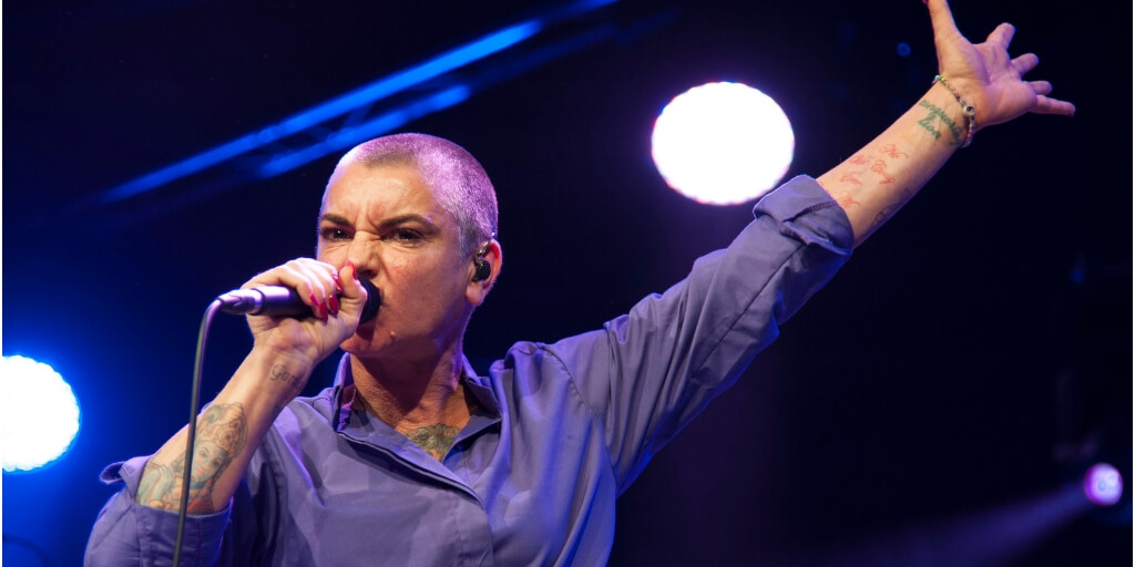 Musician Sinead O'Connor singing on stage, holding a microphone, with her left arm in the air, hand splayed. She has a shaved head, wears a blue button down, has tattoos on both arms, and has a severe angry expression.