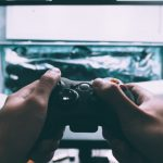 A image of a person's hands holding an X-Box game controller. In front of them is a television with a game playing