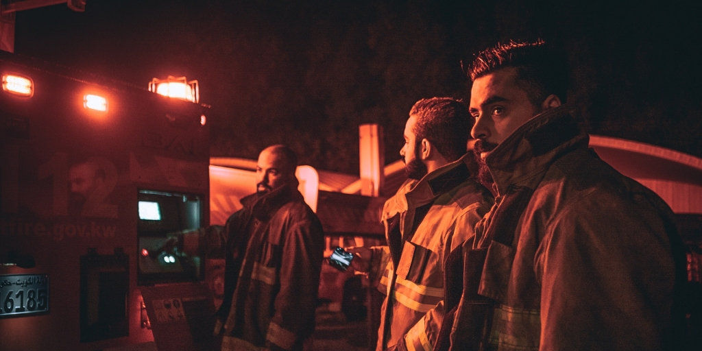 Image of three firemen standing by a firetruck at night. They are in uniform and look apprehensive