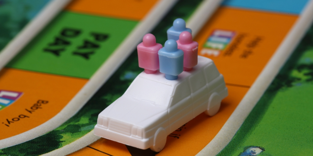 A close-up of the board game The Game of Life. There is a white game piece in the shape of a car with three plastic pegs in it to represent people