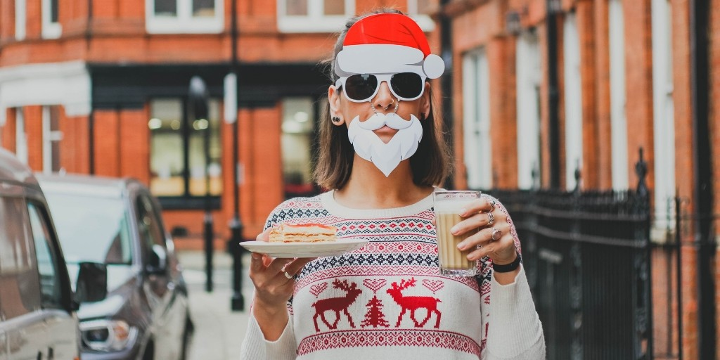 A person with short brown hair stands on a city street holding a plate of dessert and a glass of iced coffee. She wears a Christmas reindeer sweater and a pair of sunglasses with a fake beard and Santa hat attached to it
