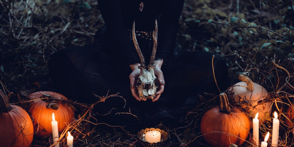 A person wearing a long black long-sleeved dressed with black painted nails kneels on the ground, holding a deer skull. In front of them is a candle in a holder, surrounded by pumpkins, lit candlesticks and dried up roots.