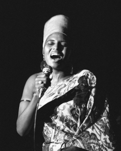 [Image description: a black and white image of singer Miriam Makeba donned in a printed wrap as she sings on a stage] via Instagram / @unlockthenow