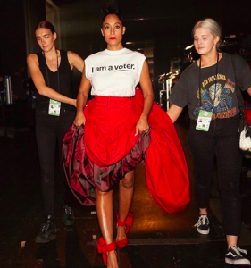 "[Image description: Tracee Ellis Ross wearing a shirt that reads ""I am a voter."" with a red skirt and red heels.]"